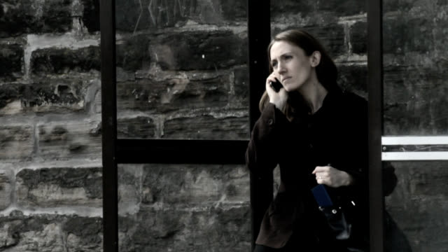 Woman receive bad phone call at a bus stop