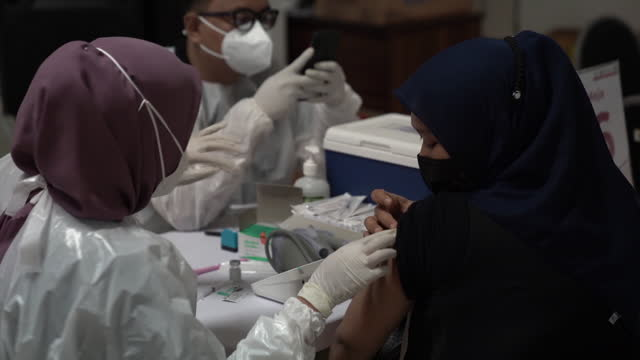 woman receives a dose of the astrazeneca plc covid-19 vaccine during a vaccination drive hosed by indonesian retail merchants association in jakarta,... - human arm stock videos & royalty-free footage