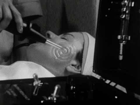 A woman receives an electronic facial treatment at a beauty salon