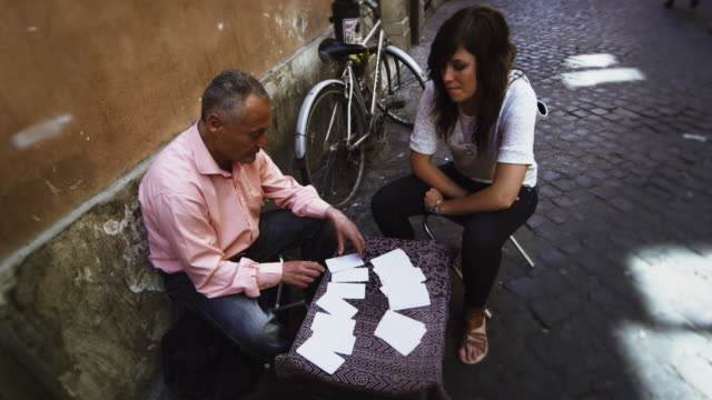 woman receives her fortune on a roman street - tarot cards stock videos & royalty-free footage