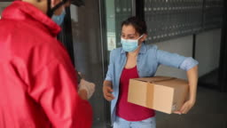 Woman receiving a package from delivery person during Covid-19 pandemic