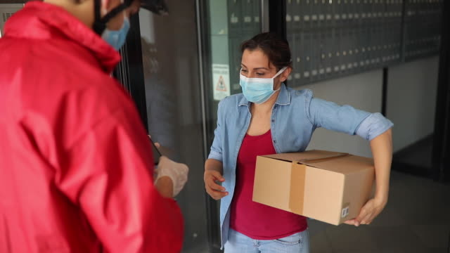 woman receiving a package from delivery person during covid-19 pandemic - delivering stock videos & royalty-free footage