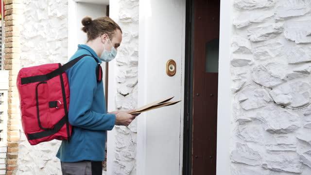 vídeos y material grabado en eventos de stock de una mujer recibiendo un paquete del repartidor - trabajador de correos