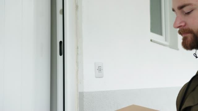 vídeos y material grabado en eventos de stock de mujer recibiendo un paquete en casa, dando su firma en el teléfono inteligente - entrega digital - recibir