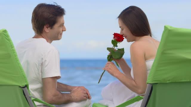 vídeos de stock, filmes e b-roll de hd: mulher receba uma rosa na praia - cadeira dobrável