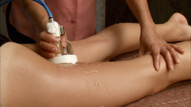 vidéos et rushes de cu woman receiving anti-cellulite treatment / brussels, belgium - massage room