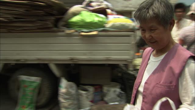 stockvideo's en b-roll-footage met ms zo pan woman receiving cash for recyclable goods at recycling stand, beijing, beijing, china - minder dan 10 seconden