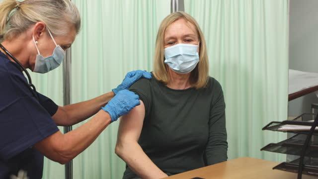 vídeos de stock e filmes b-roll de woman receiving covid-19 vaccination injection - membro humano
