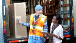 Woman receiving delivery from truck driver