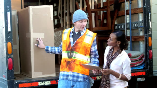 woman receiving delivery from truck driver - removal man stock videos & royalty-free footage