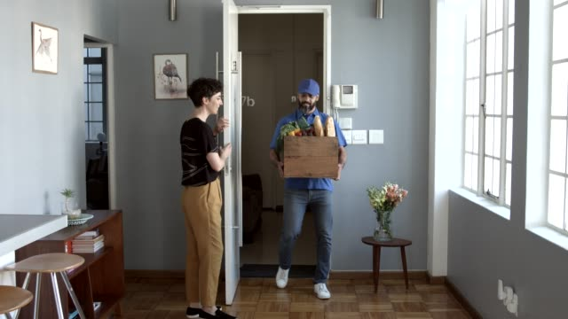 vídeos y material grabado en eventos de stock de woman receiving groceries from delivery man at home - entrada