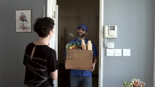 vídeos de stock, filmes e b-roll de woman receiving groceries from delivery man in apartment - entregador