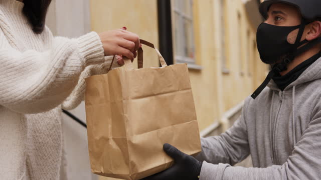 woman receiving her food from bike delivery man - paper bag stock videos & royalty-free footage