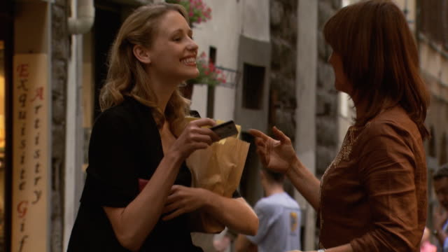 a woman receiving her goods and credit card back - see other clips from this shoot 1150 stock videos and b-roll footage