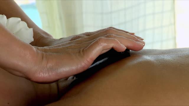 vídeos y material grabado en eventos de stock de cu pan woman receiving hot stone therapy / cape town, south africa - lastone therapy