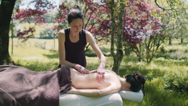 woman receiving massage outside - massaging stock videos & royalty-free footage