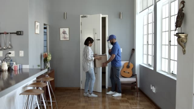 Woman receiving parcel from delivery man at home