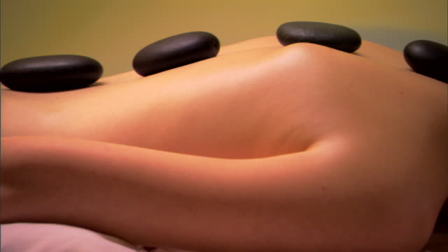 woman receiving stone massage treatment - lastone therapy stock videos and b-roll footage