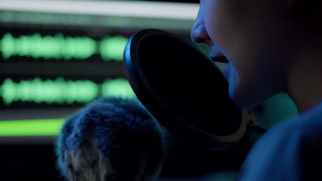 vídeos y material grabado en eventos de stock de mujer grabando podcasting en la computadora con micrófono - foto de estudio