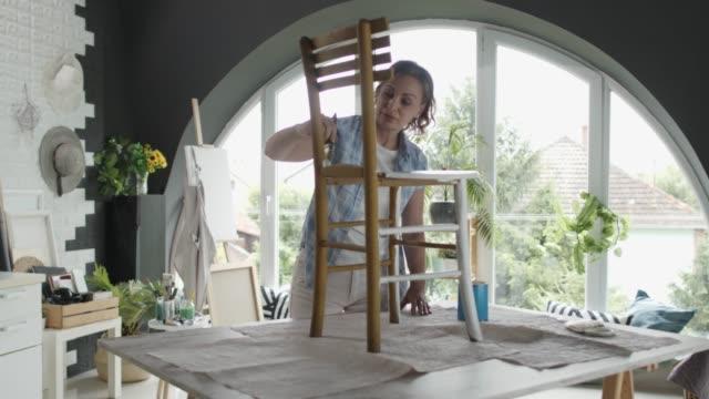 donna ricicla vecchia sedia dipingendolo di bianco - craft video stock e b–roll