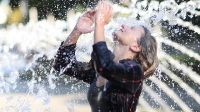 woman refreshes under a fountain - erfrischung stock-videos und b-roll-filmmaterial