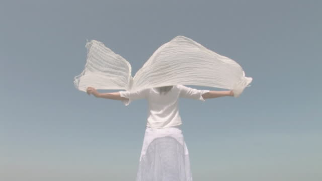 Woman refreshing herself with shawl streaming in wind
