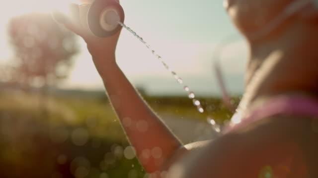 slo-mo-frau selbst mit spritzer wasser erfrischend - nass stock-videos und b-roll-filmmaterial