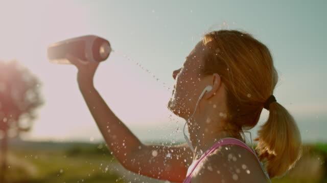 vídeos de stock, filmes e b-roll de slo mo mulher refrescando-se com esguicho de água - sedento