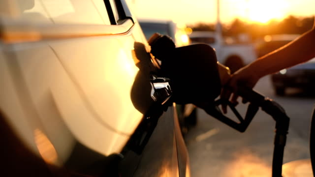 woman refueling car at gas station pump at sunset - industria petrolifera video stock e b–roll