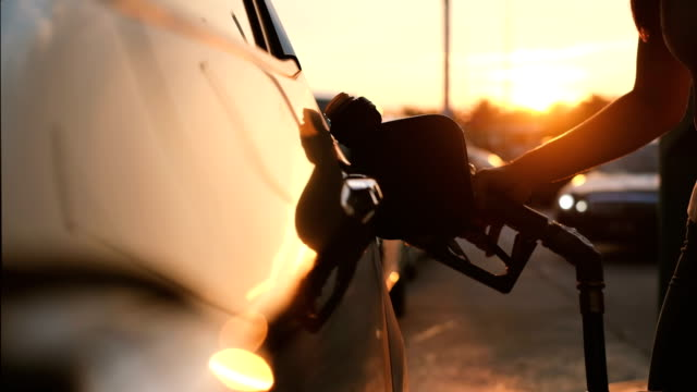 woman refueling car at gas station pump at sunset - automobile industry video stock e b–roll