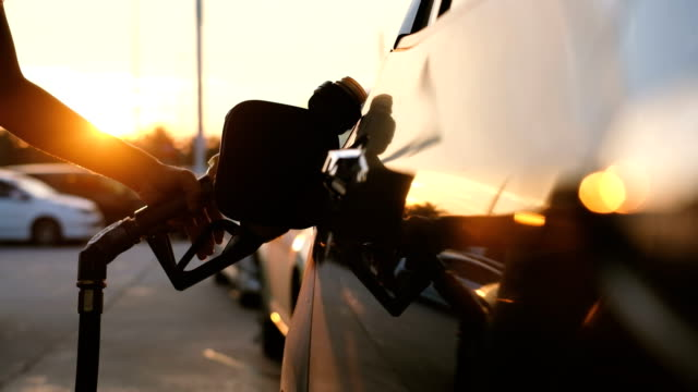 woman refueling car at gas station pump at sunset with flare - petrol station stock videos & royalty-free footage