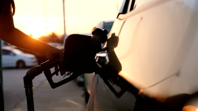 vídeos de stock e filmes b-roll de woman refueling car at gas station pump at sunset with flare - gas station