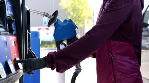 vídeos y material grabado en eventos de stock de mujer refueling car en gas station con guantes de protección durante covid-19 - echar combustible