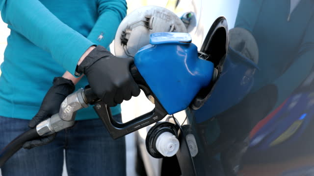 vídeos de stock e filmes b-roll de woman refueling car at gas station with protective gloves during covid-19 - bomba petrolífera