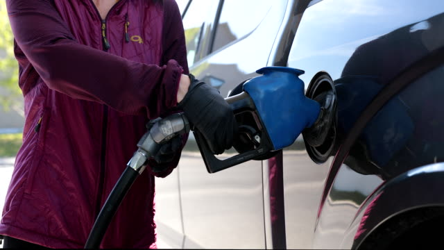 woman refueling car at gas station with protective gloves during covid-19 - glove video stock e b–roll