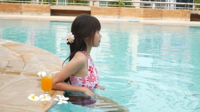 女性はリラックスしてスイミングプールで楽しむ - 生い茂る点の映像素材/bロール