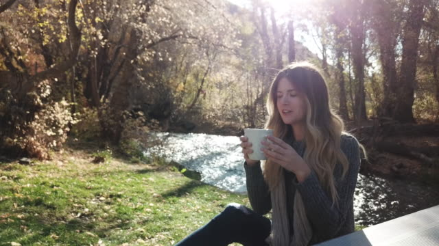 Woman relaxed on bench outdoors with coffee and phone