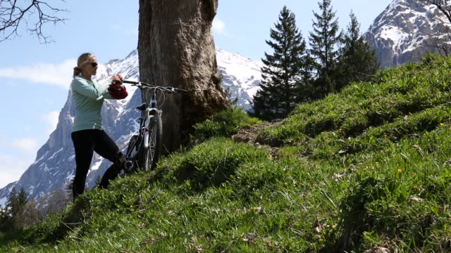 woman relaxes after mountain bike ride, below snow capped mountains - only mature women stock videos & royalty-free footage