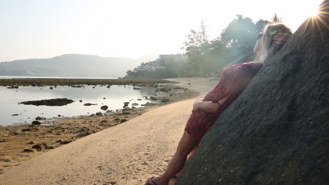 Woman relaxes against boulder, looks out to sea