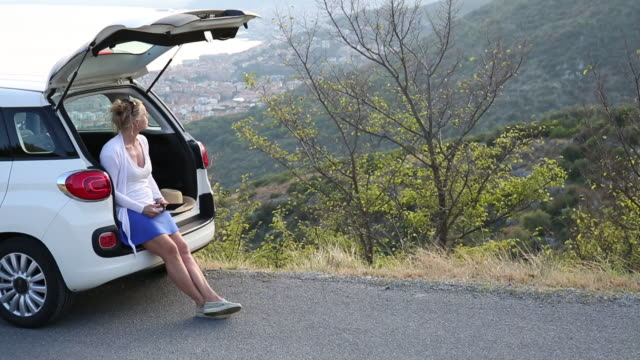Woman relaxes against car tailgate, with digital tablet