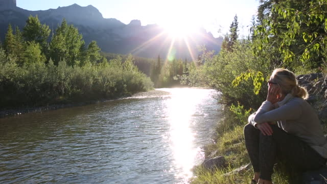 woman relaxes at edge of mountain creek, sunrise - turtleneck stock videos & royalty-free footage