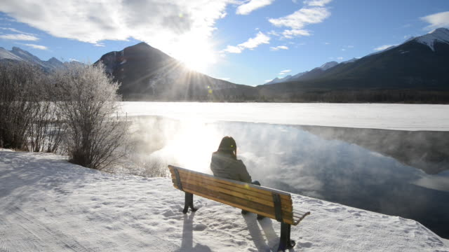 Woman relaxes at lake bench, steam rising, sunrise