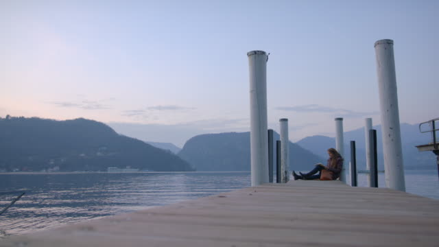 woman relaxes at the end of a dock, view of lake and mountains - reading stock videos & royalty-free footage