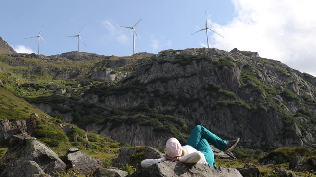 woman relaxes below wind turbines, in mountain meadow - lying on back stock videos & royalty-free footage