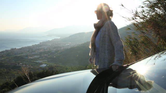 woman relaxes by car, looks off towards sea - hood clothing stock videos and b-roll footage