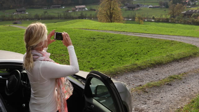 woman relaxes by car on rural road, mountain road - see other clips from this shoot 56 stock videos & royalty-free footage