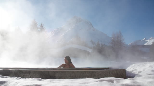 a woman relaxes in a hot tub hot tub at a spa. - bagno caldo video stock e b–roll