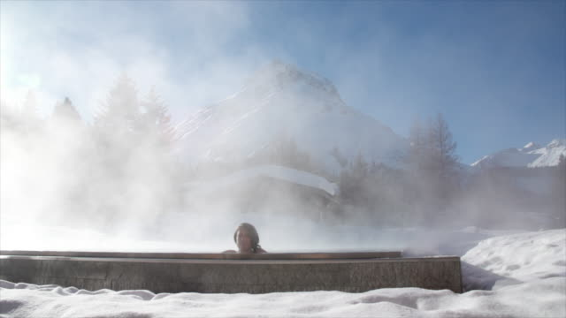 a woman relaxes in a hot tub hot tub at a spa. - whirlpool stock-videos und b-roll-filmmaterial
