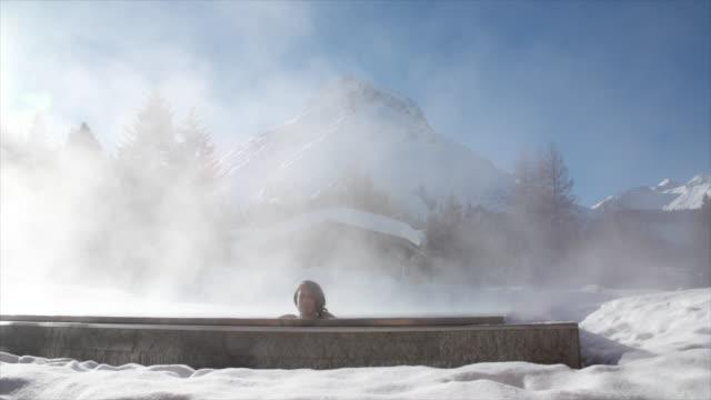 a woman relaxes in a hot tub hot tub at a spa. - ジャクジー点の映像素材/bロール