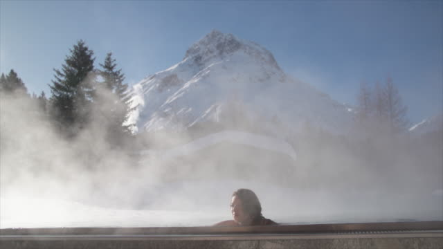 A woman relaxes in a hot tub jacuzzi at a spa.